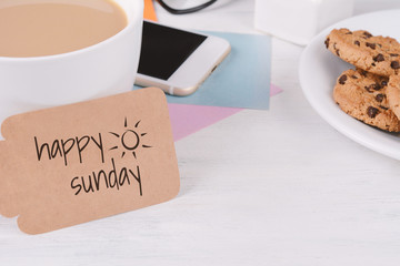 "Paper card with ""happy sunday"" text and coffee with phone, cookies and glasses"