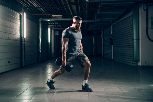 Side view of muscular attractive caucasian bearded man doing lunges with dumbbells in underground hallway. Storage units and pipes in background.