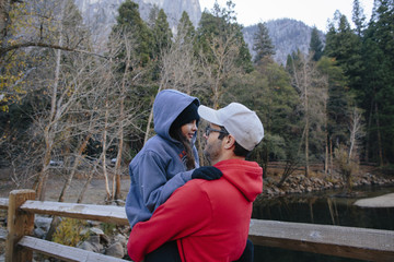 Father carrying daughter while standing in forest at Yosemite National Park