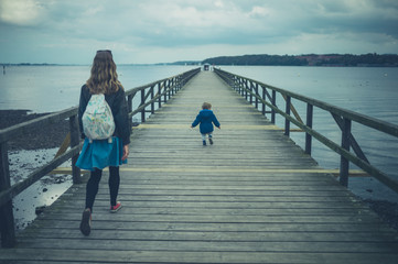 Toddler and mother walking on pier