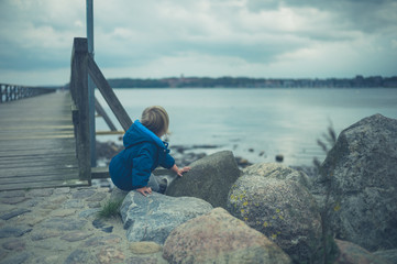 Little toddler playing on pier in autumn