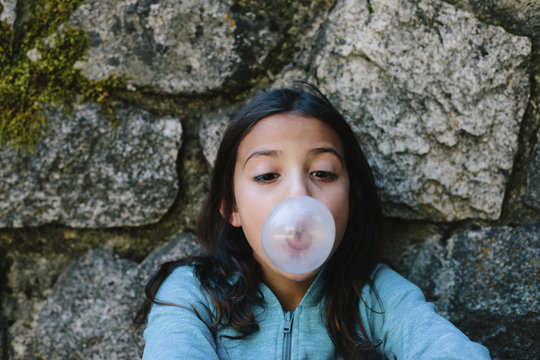 Playful girl blowing bubble gum against stone wall in forest at Yosemite National Park