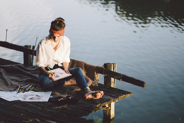 High angle view of woman drawing while sitting on pier over lake during sunset