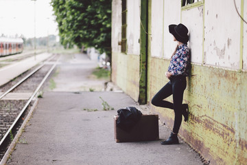 Side view of woman with suitcase standing by wall on railroad station