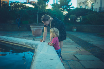 Young woman playing with toddler by fountain