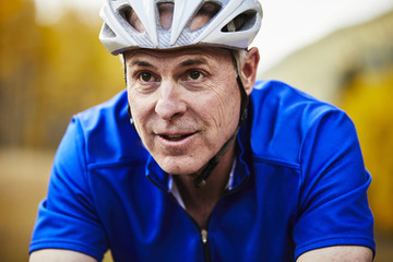 Close-up of senior man wearing bicycle helmet cycling in forest