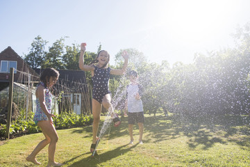 Siblings playing with sprinkler in yard during sunny day