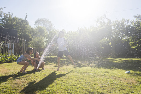 Siblings playing with sprinkler in yard against sky during sunny day