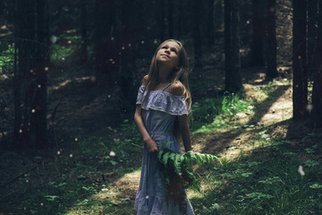 Girl holding plants while looking up in forest