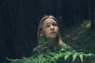 Close-up of girl with plants looking away while standing in forest