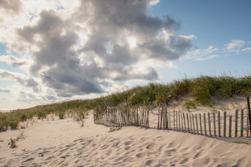 sand dunes with beach fence with blue sky and clouds