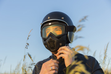 Low angle view of male biker fastening helmet while standing against clear blue sky during sunset