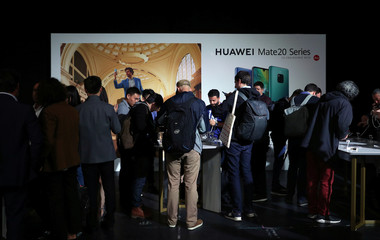 People look at display models of Huawei Mate20 smartphone series at a launch event in London