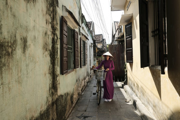 Woman with bicycle wearing Asian style conical hat while walking amidst houses at alley