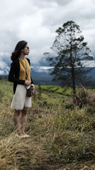 Full length of young woman looking at view while standing on grassy field against cloudy sky