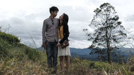 Young couple standing on grassy field against cloudy sky