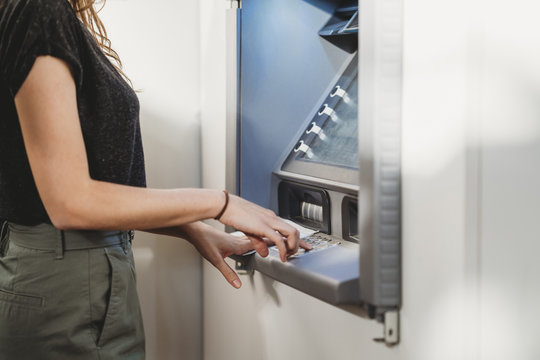 Midsection of woman using ATM