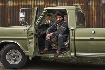 Portrait of confident carpenter sitting in pick-up truck