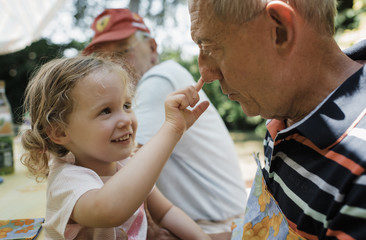 Cute granddaughter touching grandfather's nose while sitting in yard