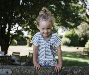 Portrait of smiling girl standing on wooden bench against trees at park