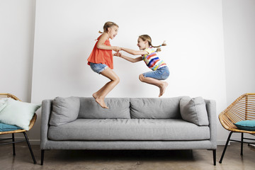 Side view of happy sisters holding hands while jumping on sofa against wall at home