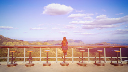 Girl was sitting on the chairs in balcony overlooking the hills and sky.