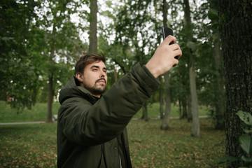 Man taking selfie in green woods