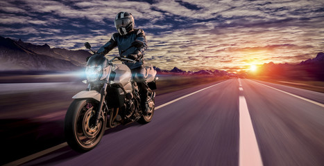 motorcyclist rides home in the evening on a highway while sunset