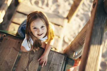 High angle portrait of happy girl sitting on wooden outdoor play equipment at playground during sunset