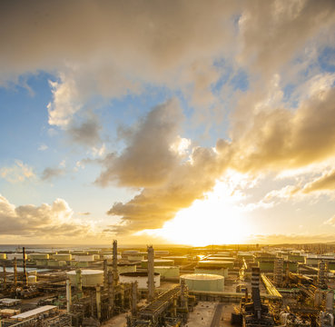 Petrochemical plant against cloudy sky during sunset