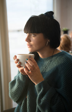Cuddling woman in sweater drinking coffee