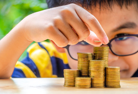 The Asian boy stacking with coins to save the money for the future. Concept for loan, property ladder, financial, mortgage, real estate investment, taxes and bonus.