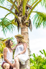 Young romatic couple tourist under the coconut palm. Bright green and yellow picture. Bali island. Indonesia.