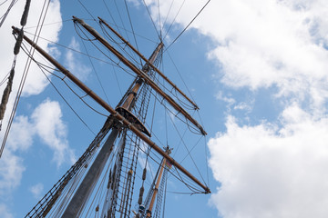mast and rigging of an historic  sailing ship against the blue sky with clouds, adventure voyage concept, copy space