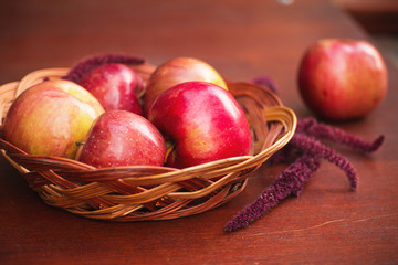 Apples in a basket on a wooden table