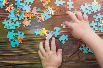 A child's hand collects a puzzle on a wooden background.