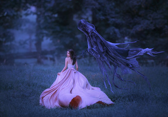 Beautiful girl in a long, pink, fluttering dress runs away from death in the form of a dark demon who came out of hell. Frightened brunette girl looks around. Artistic, gothic photo in cold colors