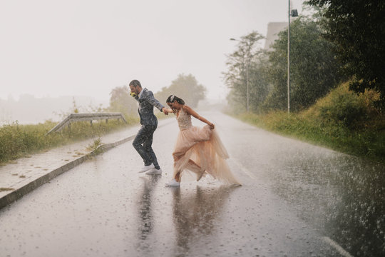 Silly young just married couple crossing road on rainy day. Running in wet ceremonial clothes.