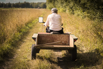 farmer man in work clothes riding on a motor-block with a trailer