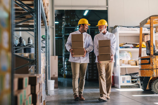 Picture of two male warehouse workers with helmets on their heads carrying boxes in their hands. Talking and walking.