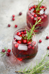 In de dag Cocktail Cold refreshing drink with cranberries and rosemary on a gray concrete background