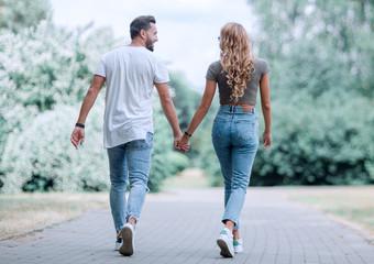 Obraz Couple in love walking in park holding hands - fototapety do salonu