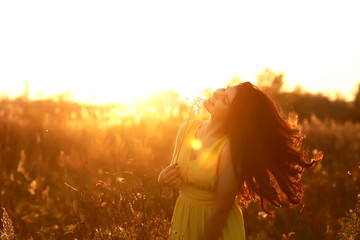 Fashion Lifestyle, Portrait of Beautiful Young Woman with long dark hair Backlit at Sunset Outdoors. Soft warm sunny colors