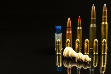 Chess pieces and ammunition on a black background. Play chess. Checkmate. The concept of defeat and victory. Dangerous game.