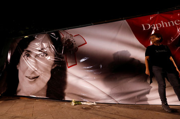 People reveal a banner with the picture of anti-corruption journalist Daphne Caruana Galizia on the place of her makeshift memorial during a vigil and protest on the first anniversary of her death in a car bomb, in Valletta