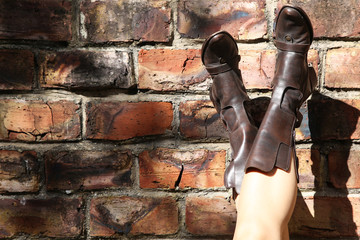 A carefree women resting her leather boots on a brick wall.