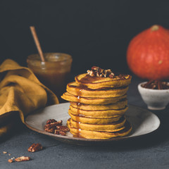 Pumpkin spice pancakes with caramel and pecan nuts. Toned, square crop