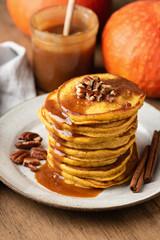 Pumpkin spice pancakes with caramel sauce and nuts on a plate, closeup view, selective focus. Autumn comfort food