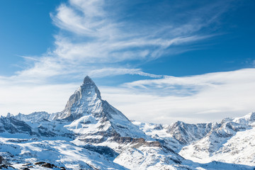 Scenic view on snowy Matterhorn peak in sunny day with blue sky and dramatic clouds in background, Switzerland.