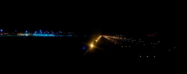 Fotobehang Luchthaven airport runway illuminated by bright landing lights at night